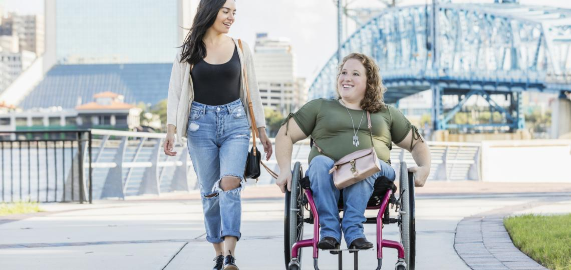 two women on a sidewalk, one in a wheelchair
