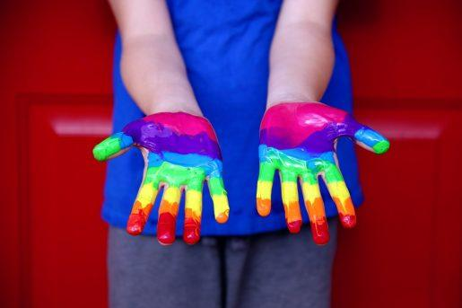 This image shows a child's hands painted with the colors of the rainbow.