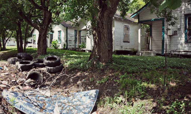 photo of houses in poor condition, trash, tires